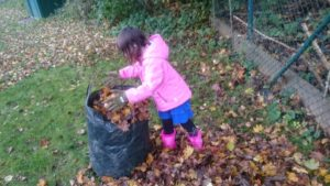 Ein Kind beim Laubaufsammeln