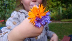 Ein Kind hat Blumen in der Hand
