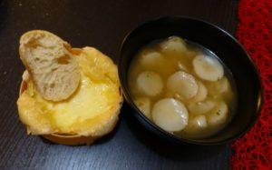 Suppe in der Schüssel, Ofenkäse und eine Brotscheibe
