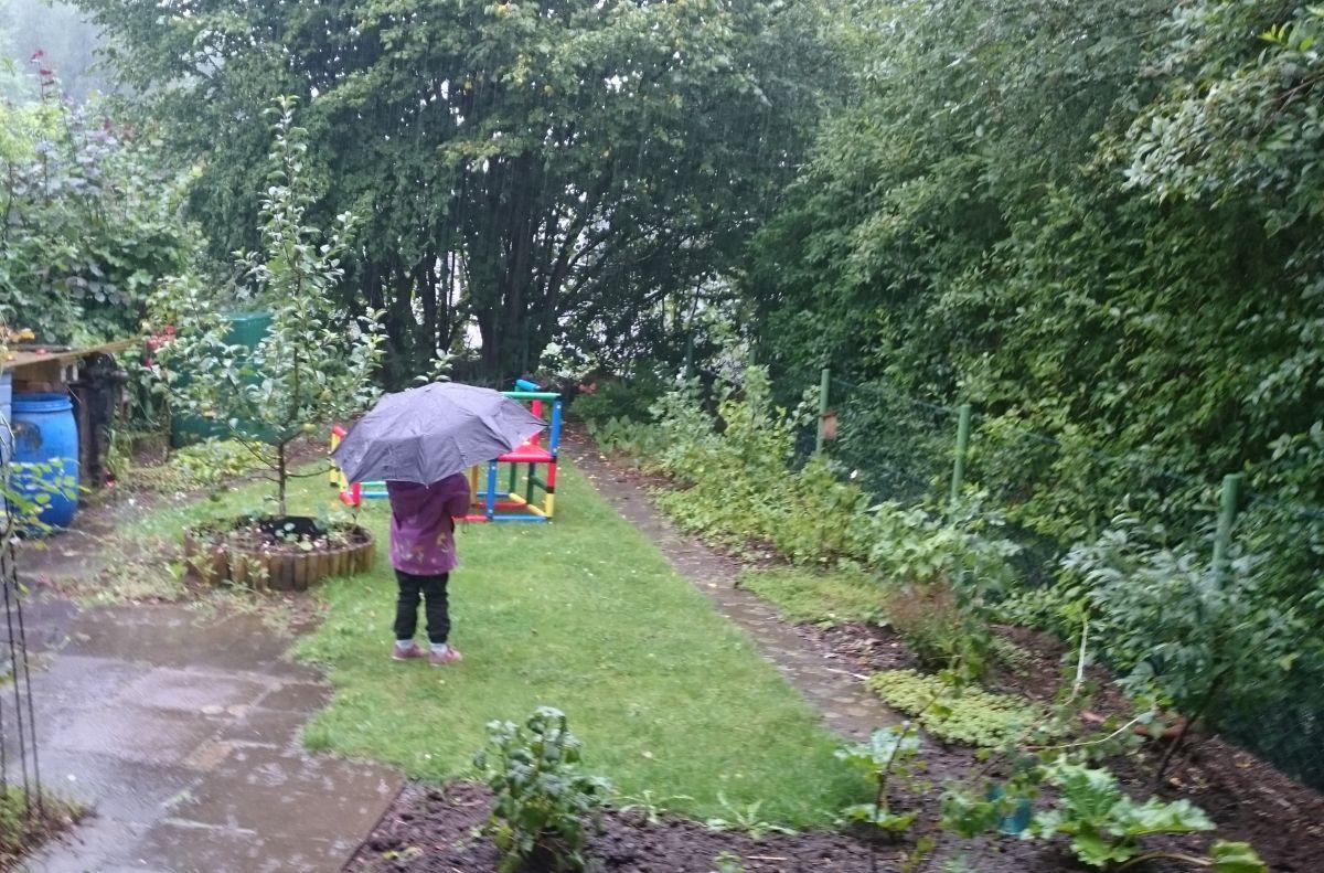 Starkregen-Kind mit Schirm